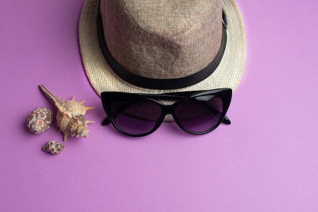 Sommeraccessoires, muscheln, hut und sonnenbrille. sommerferien und seekonzept. Premium Fotos