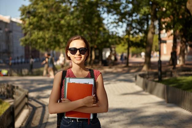 Sommerbild im freien der entzückenden niedlichen kaukasischen studentin, die stilvolle schatten, rucksack, gepunktetes oberteil und jeans trägt, die zu fuß zum college pendeln, hefte tragen, lächeln, schönes wetter genießen Kostenlose Fotos