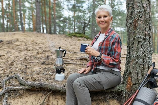 Sommerbild im freien der fröhlichen frau mittleren alters in der aktivkleidung, die unter baum mit campingausrüstung und kessel auf gasbrenner entspannt, becher hält, frischen tee genießt, ruhe beim wandern allein hat Kostenlose Fotos