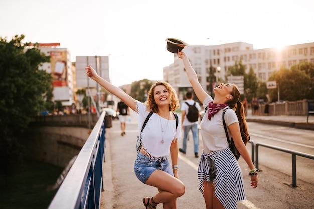 Sommerferien, feiertage, partei, festival und leutekonzept. zwei mädchen tanzen auf der stadtbrücke. Premium Fotos