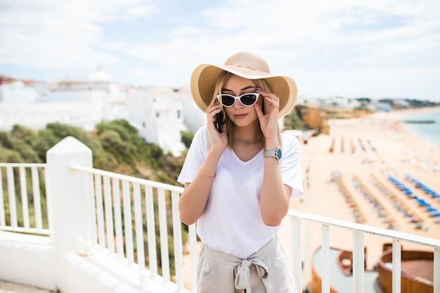 Sommerferienfrau, die handy-sms-nachricht draußen auf balkonterrasse verwendet Kostenlose Fotos