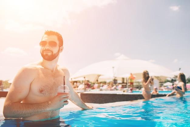 Sommerfoto des muskulösen lächelnden mannes im schwimmbad Premium Fotos