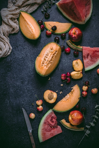 Sommerfrüchte wie melone, rote wassermelone, kirschen auf schwarzer oberfläche. Premium Fotos
