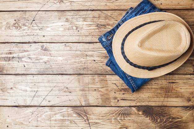 Sommerkleidung für frauen. flaches laienmode-foto. blue jeans und sonnenhut auf hölzernem hintergrund. platz kopieren Premium Fotos