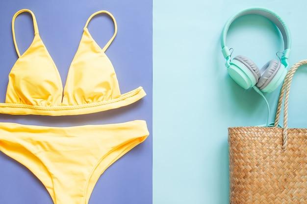 Sommerkollektion, bikini in gelber farbe, kopfhörer und strandtasche aus stroh. sommerurlaub Premium Fotos
