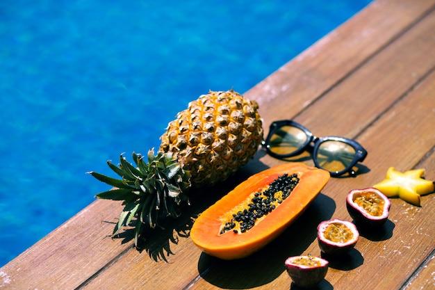 Sommerkomposition in der nähe von pool und holzboden, stilvolle hipster-sonnenlasse. Kostenlose Fotos