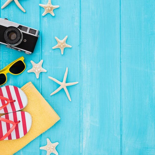 Sommerkonzept mit weinlesekamera, sonnenbrille, tuch, starfish auf blauem hölzernem hintergrund Kostenlose Fotos