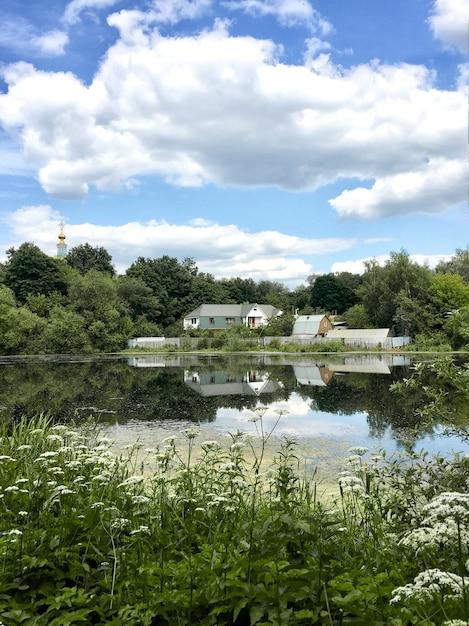 Sommerlandschaft mit bauernhaus im seewasser reflektiert Premium Fotos