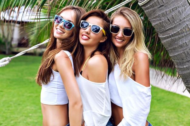 Sommerlebensstilporträt des baumes hübsche junge freundinnen, die spaß zusammen an schönem sommertag im tropischen land haben, drei frauen genießen ihren urlaub, bereit für party. Kostenlose Fotos