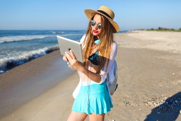 Sommerlebensstilporträt des hübschen blonden mädchens, das am einsamen strand nahe ozean aufwirft, bikinioberteil, hellen rockhut und sonnenbrille tragend hält, kopfhörer und tablette hält Kostenlose Fotos