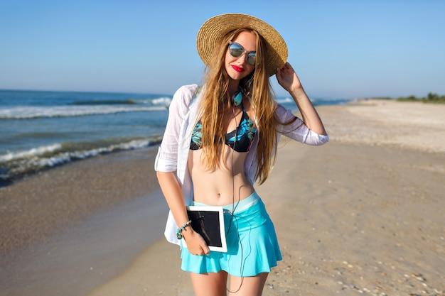 Sommerlebensstilporträt des hübschen blonden mädchens, das am einsamen strand nahe ozean aufwirft, bikinioberteil, hellen rockhut und sonnenbrille tragend, kopfhörer und tablet hält, urlaub freiberufliche stimmung Kostenlose Fotos
