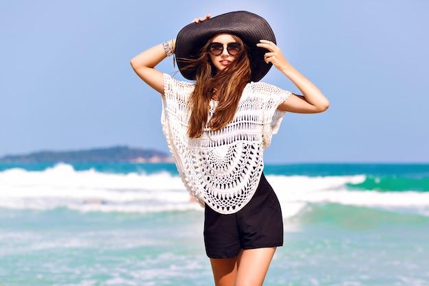 Sommermodeporträt der schönen frau genießen windigen sonnigen tag nahe ozean, urlaubsstil. junges stilvolles mädchen, das schwarzen strampler-weinlesehut und große sonnenbrille, helle farben trägt Kostenlose Fotos
