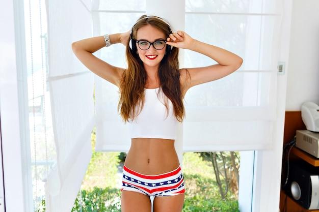 Sommermodeporträt des jungen hipster-mädchens mit heißem sexy körper mit perfekter passform, stilvoller vintage-brille, hellen mini-shorts und crop-top, die ihre lieblingsmusik über kopfhörer hört. Kostenlose Fotos