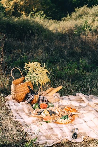Sommerpicknick bei sonnenuntergang auf dem sonnigen wetter des plaid-, lebensmittel- und getränkekonzeptionslebensstils Premium Fotos