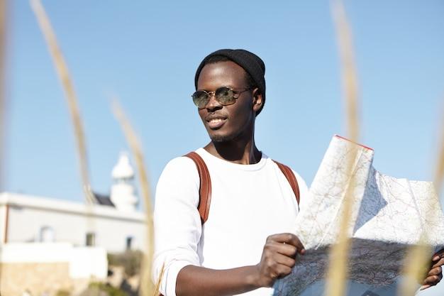 Sommerporträt des jungen mannes, der stadtführer beim sightseeing im ferienort verwendet Kostenlose Fotos