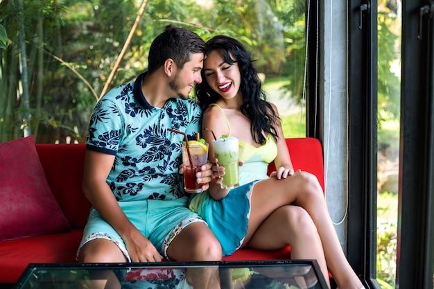 Sommerporträt des jungen mannes und der jungen frau genießen ihr romantisches date, posieren im stilvollen café, trinken cocktails, feiern spaßzeit. Kostenlose Fotos