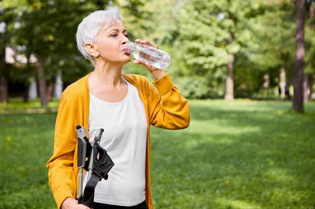 Sommerporträt einer müden grauhaarigen kaukasischen frau in ihren sechzigern, die wasser aus plastikflasche trinkt, sich nach körperlicher aktivität erfrischt und mit nordischen spazierstöcken im freien posiert Kostenlose Fotos