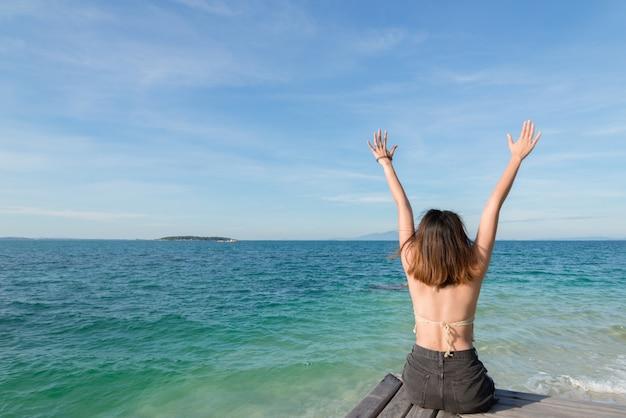Sommerporträt im freien der jungen hübschen frau, die zum ozean tropischem strand betrachtet Premium Fotos