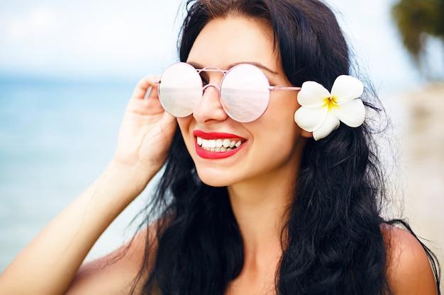 Sommerporträt ist hübsches brünettes mädchen, das auf perfektem einsamen tropischen inselstrand aufwirft, reist und genießt urlaub, strahlend blauen bikini und sonnenbrille. Kostenlose Fotos