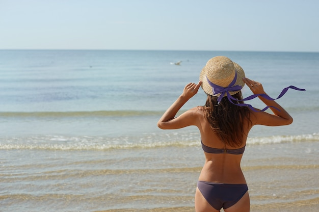 Sommerporträtfrau in einem hut betrachtet das meer Premium Fotos
