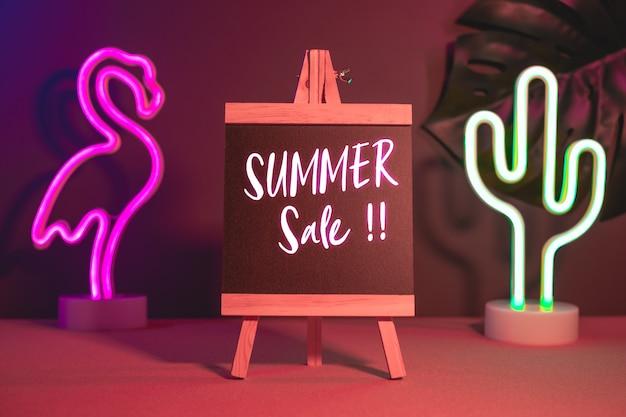 Sommerschlussverkauf auf tafel mit flamingo- und kaktusneonrosa und blaulicht auf tabelle Premium Fotos