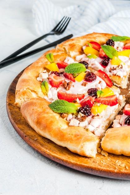 Sommersnacks. essen für die party. fruchtpizza mit sahne, korinthen, joghurt und früchten Premium Fotos