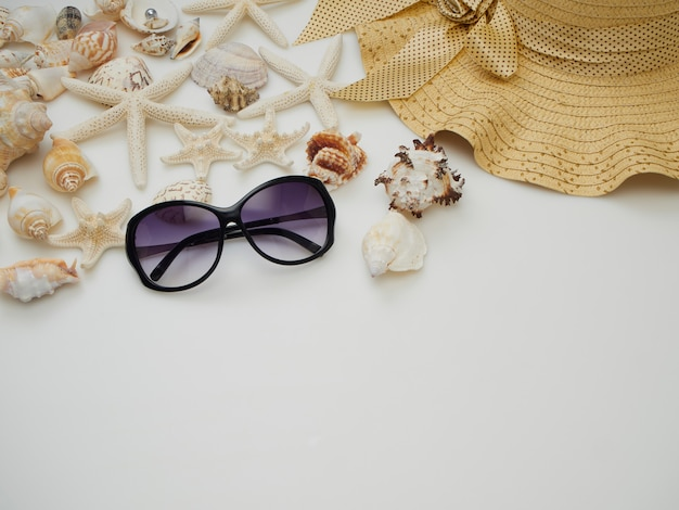 Sommerstrandkleideinzelteile - oberteile, starfish, sonnenbrille, strohhüte auf einem weißen hintergrund Premium Fotos