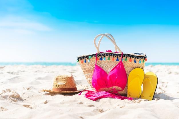 Sommertasche, pantoffel, hut und bikini am tropischen strand mit hintergrund des blauen himmels. Premium Fotos