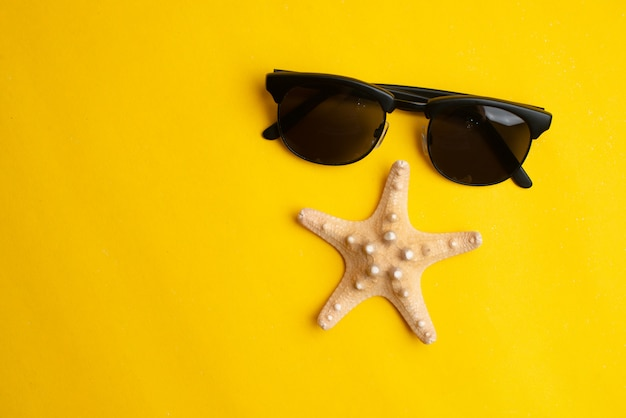 Sommerzubehör, muschel und sonnenbrille auf gelber oberfläche. Premium Fotos