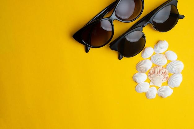 Sommerzubehör, oberteile und paarsonnenbrillen auf gelbem hintergrund. sommerferien, honigmond und seekonzept. Premium Fotos