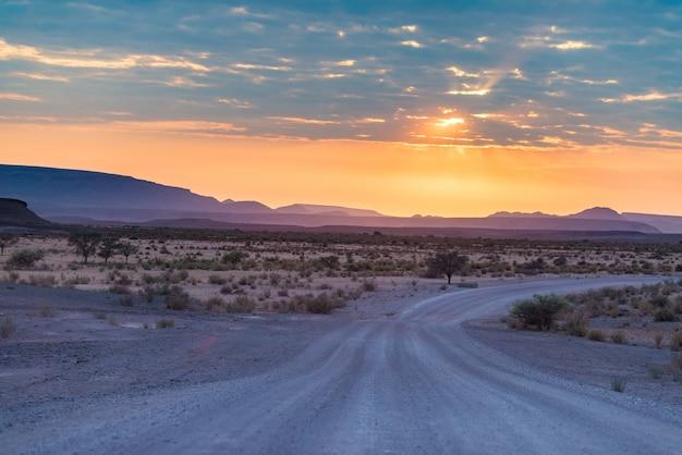 Sonnenaufgang über der namib-wüste, roadtrip im wunderbaren nationalpark namib naukluft, reiseziel in namibia, afrika. morgenlicht, nebel und nebel, abenteuer im gelände. Premium Fotos