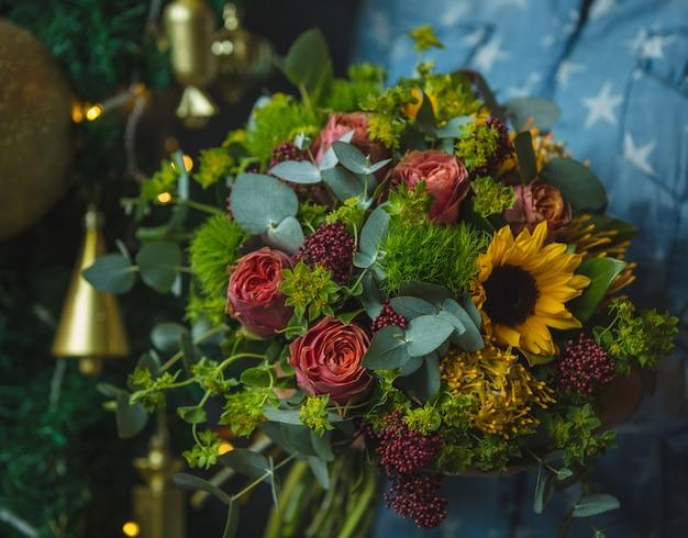 Sonnenblumen- und rosenblumenstrauß im weihnachtshintergrund bild Kostenlose Fotos