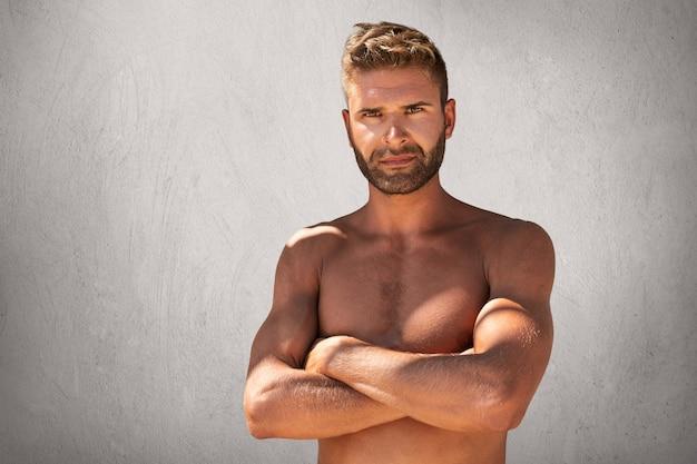 Sonnenbräuner, selbstbewusster mann mit stilvoller frisur, borsten und ansprechenden augen, der oben ohne steht und die hände gekreuzt hält Kostenlose Fotos
