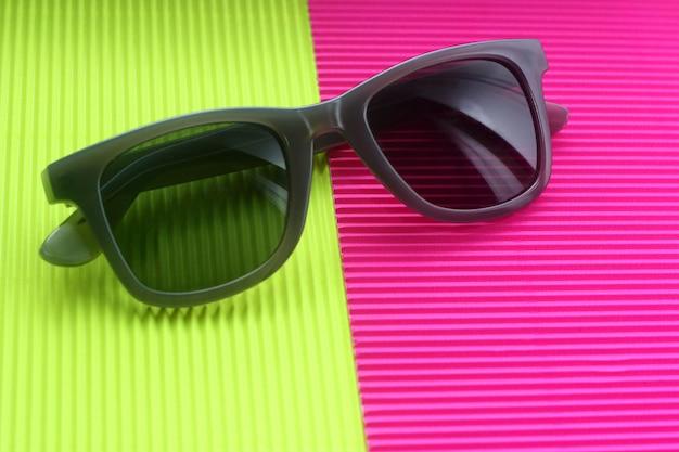 Sonnenbrille auf modischem minimalem mehrfarbenhintergrund Premium Fotos