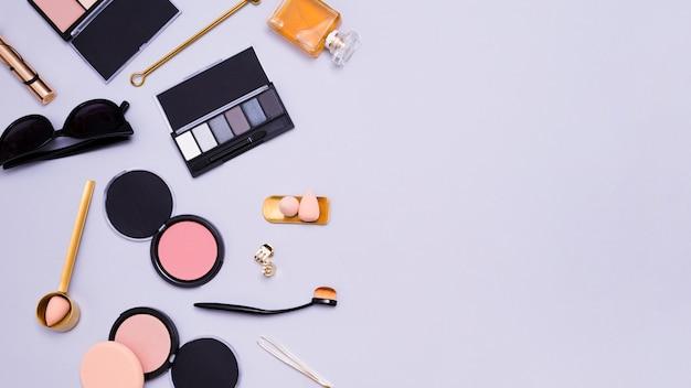 Sonnenbrille; lidschatten-palette; mixer; pinzette; clutcher; parfümflasche; make-up-pinsel und kompaktes gesichtspuder auf lila hintergrund Kostenlose Fotos