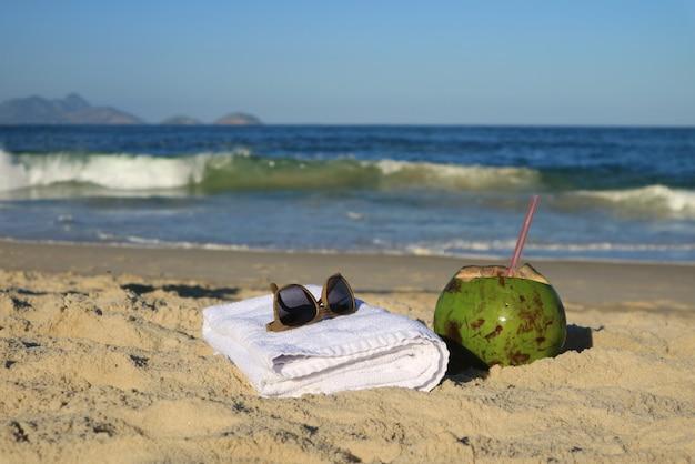 Sonnenbrille, tuch und eine frische junge kokosnuss auf dem sandigen strand, copacabana, rio de janeiro, brasilien Premium Fotos