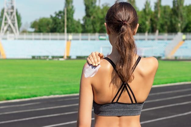 Sonnencreme sonnencreme. frau in einer sportkleidung, die sonnencreme auf schulter am schönen sommertag setzt. Premium Fotos