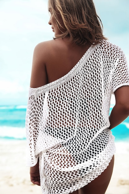 Sonnengebadete frau in der transparenten weißen bluse gehend auf sommerstrand Kostenlose Fotos