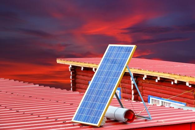Sonnenkollektor auf einem roten dach bei larung gar (buddhistische akademie) in sichuan und im roten himmel Premium Fotos