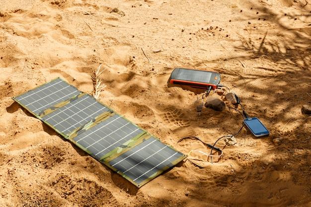 Sonnenkollektor, der aus den grund liegt und das telefon auflädt Premium Fotos