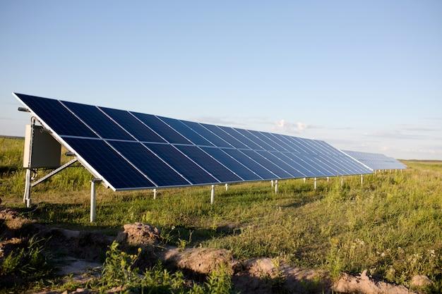 Sonnenkollektoren, blauer himmel und grünes feld. Premium Fotos