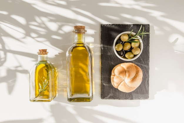 Sonnenlicht über den olivenölflaschen mit brötchen und oliven auf schieferplatte Kostenlose Fotos