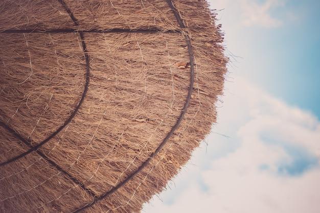 Sonnenschirm aus getrockneten blättern in der nähe des meeres. reiseurlaubskonzept. Premium Fotos
