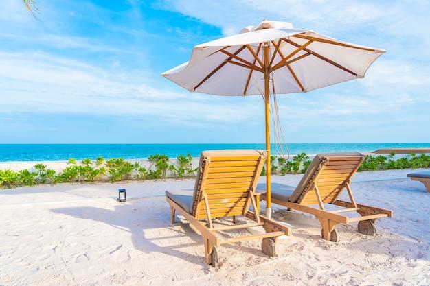 Sonnenschirm und liegestuhl um außenpool im hotelresort mit meeresmeerstrand und kokospalme Kostenlose Fotos
