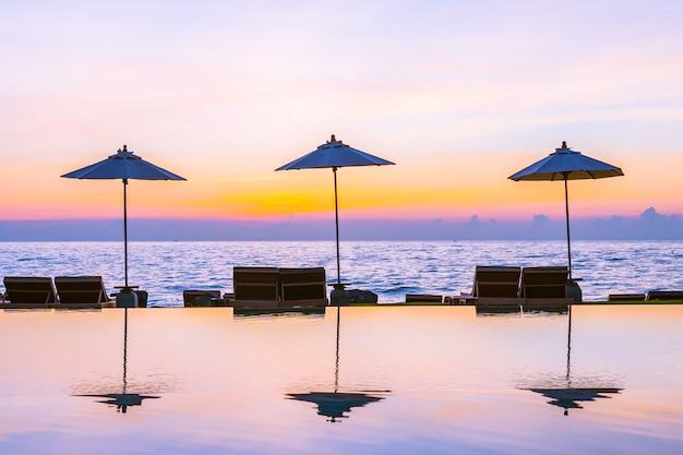 Sonnenschirm und stuhl rund um das schwimmbad im ferienhotel für urlaubsreisen und urlaub Kostenlose Fotos