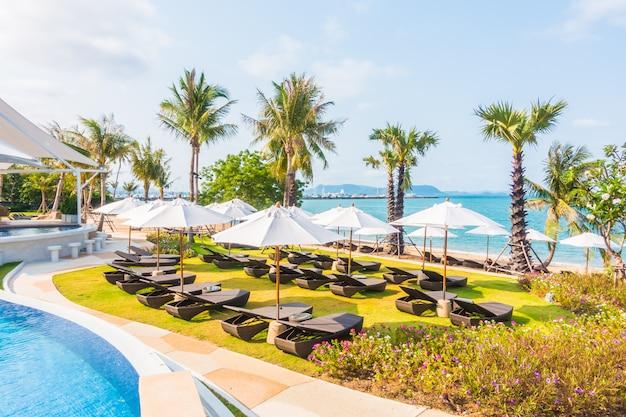 Sonnenschirm und stuhl rund um den pool Kostenlose Fotos