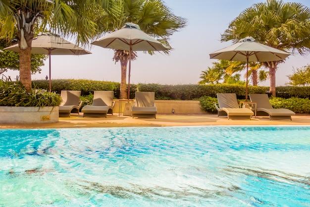 Sonnenschirm und stuhl rund um schönen luxus-pool Kostenlose Fotos