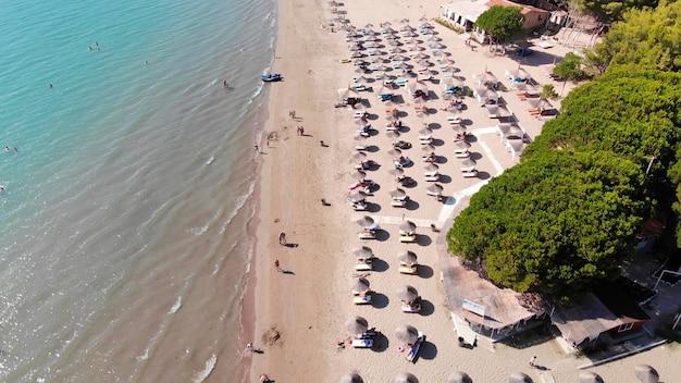 Sonnenschirme auf sand gewaschen von ruhigem klarem wasser des türkisfarbenen meeres im mittelmeer. Premium Fotos
