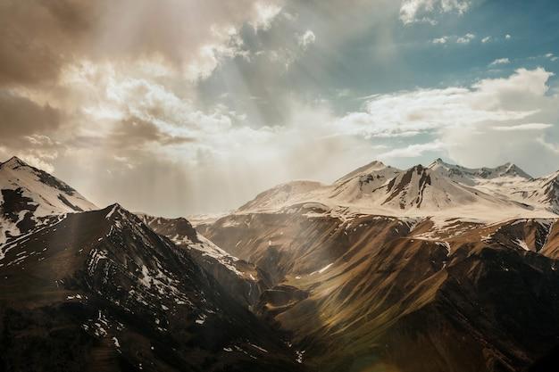 Sonnenstrahlen dringen durch die wolken in das verschneite hochgebirge Kostenlose Fotos