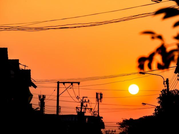 Sonnenuntergang am himmel hinter elektrischem pfosten und gebäude des schattenbildes. Premium Fotos